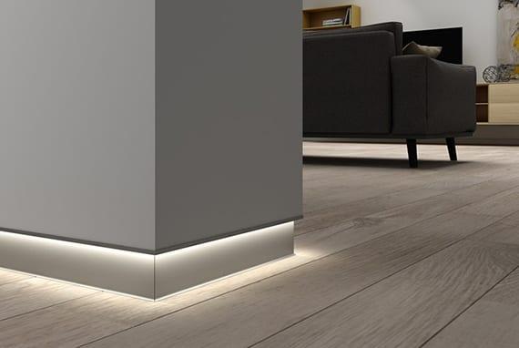 stilvolle raumgestaltung im Wohnzimmer mit holzbodenbelag, weißen Gipskartonwänden mit Alu-Sockelleiste für indirekte Beleuchtung und Polstersessel Grau