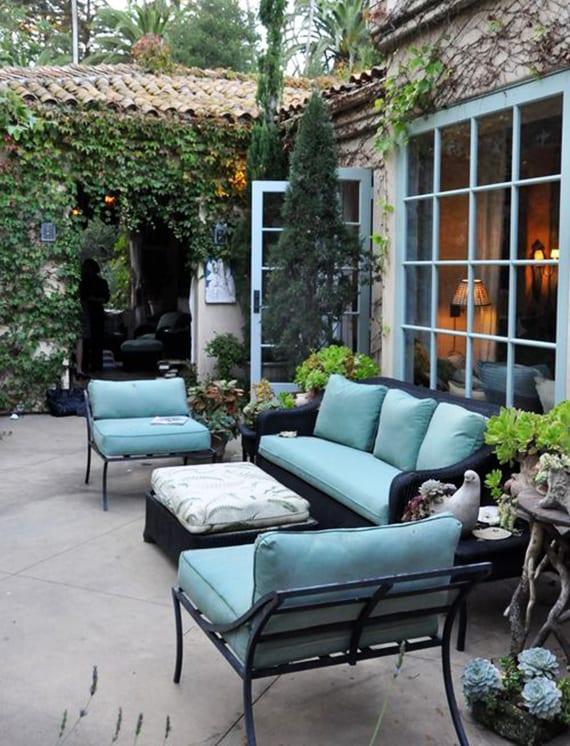 romantische terrassengestaltung im hofgarten mit schwarzem rattansofa, schwarzen gartenstühlen, polsterkissen und Sprossenfenster hellblau,kletterpflanzen und fettpflanzen