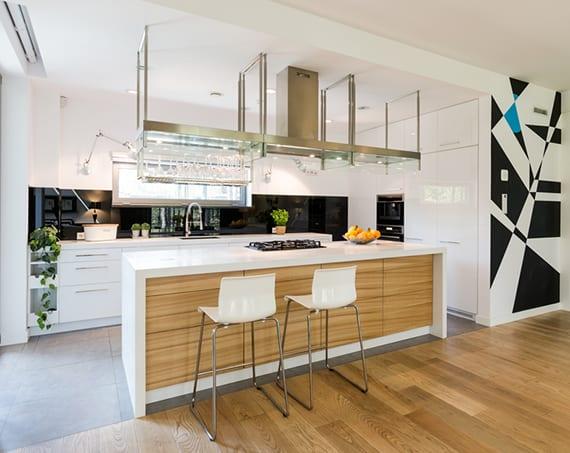 kleine Luxusküche weiß mit grauem Fliesenboden, schwarzer küchenrückwand, kochinsel weiß und holz mit tresen, deckenhaube und hängendem weinglas-halter