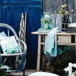 garten rustikal gestalten mit holztür blau, altem holztisch mit schubladen, klassischem holzgartenstuhl mit dekokissen