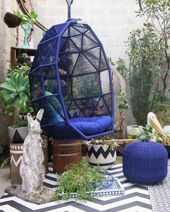 kreative gestaltung für garten und terrasse mit schaukelstul und polsterhocker in ultramarin, weißem teppich mit schwarzem fischgrätmuster, baumstümpfen und gemalten blumentöpfen