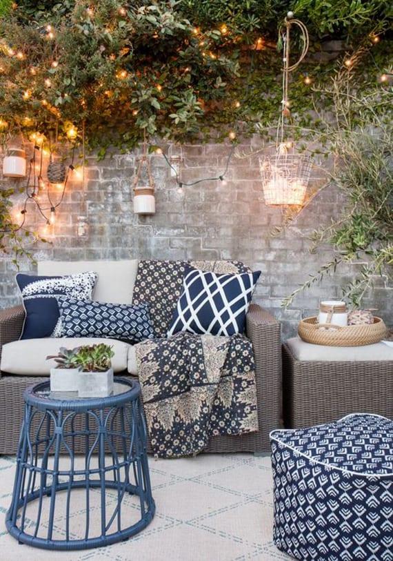 coole garten ideen für moderne garteneinrichtung mit rattanmöbeln in beige, dekokissen mit blauer Musterung, rundem beistelltisch blau und lichterkette als dekoration der grauen gartenmauer