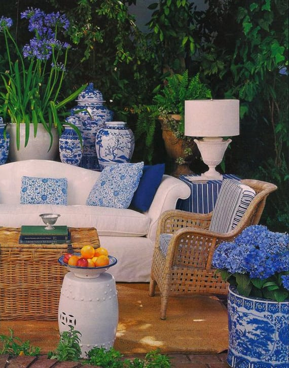 garten wohnlich gestalten in weiß und blau mit kleinem soffa weiß, holzstuhl und rattankoffer als kaffeetisch, weißer tischlampe und großen vasen und blumentöpfen aus japanischem porzellan