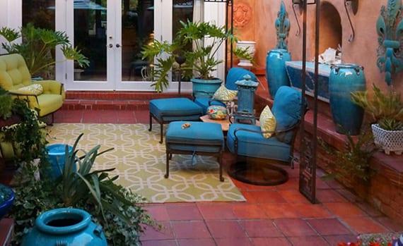 hofgarten mit gartenkamin, ziegelroten bodenfliesen, retro metallmöbel mit polstern in grün und blau, teppich grün und antiken vasen blau