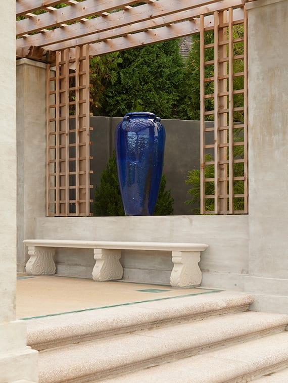 moderne asiatische gartengestaltung mit holzpergola, sitzbank aus Naturstein und große blaue Amphora