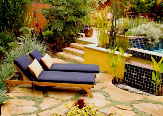 kleiner Hofgarten mit Schwimmbecken lebendig gestalten mit dunkelblauer Mosaik, Holzliegen mit blauen Polstern, holzterasse und halbrunde sonnenterrasse mit natursteinen und grüner Fuge