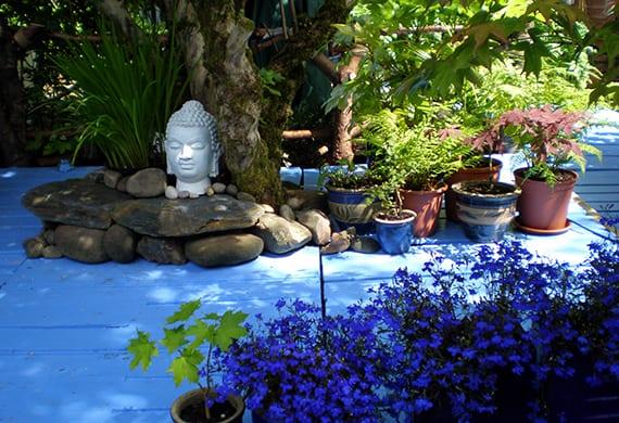 coole farbgestaltung garten mit blau gestrichenem bodenbelag, dunkelblauen blümen und kleinem steingarten mit weißem Buddhafigur und blauen blumentöpfen