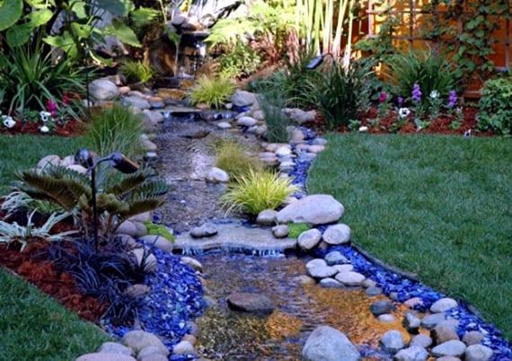 coole gartengestaltung mit wasser, steinen, blauen Glassteinen und passenden Gartenleuchten
