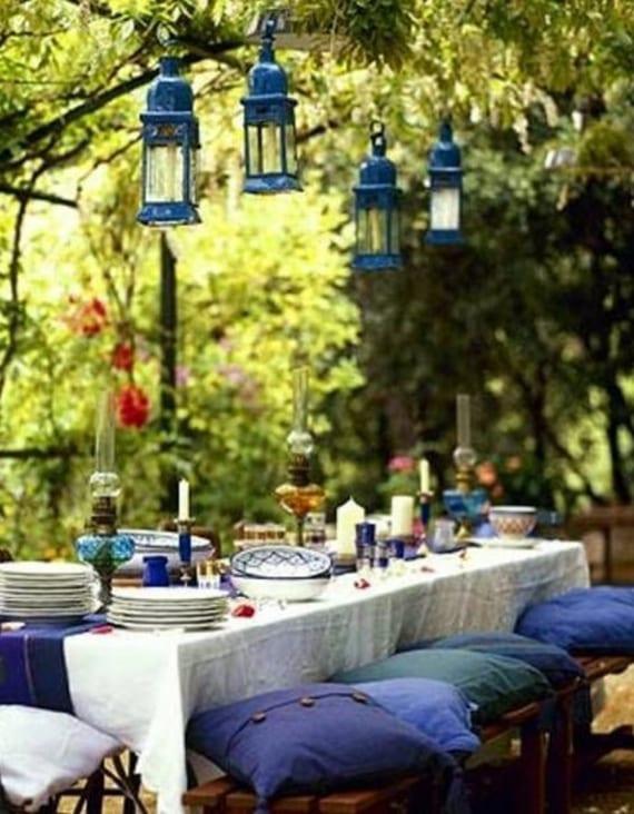 tisch eindecken im rustikalen stil mit weißer tischdecke, blauem tischläufer, holzbänken mit blauen kissen und metalllaternen blau