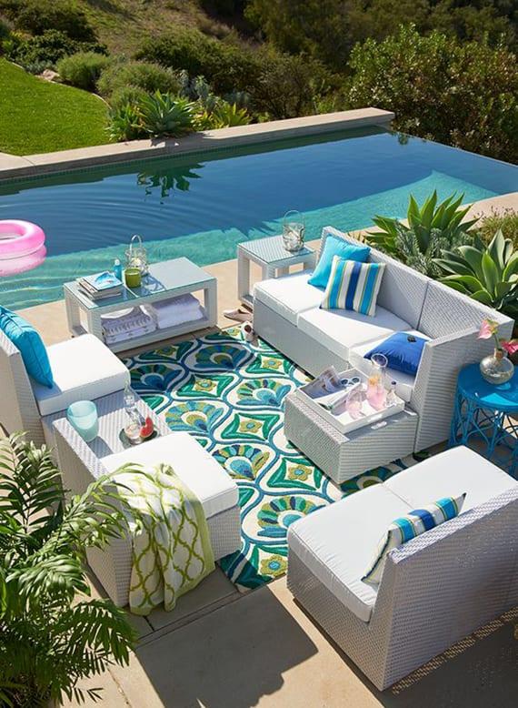 traumgarten mit pool, sonnenterrasse mit steinplatten in beige, weiße rattangartenmöbel auf teppich mit muster in grün und blau und kissen in aquablau
