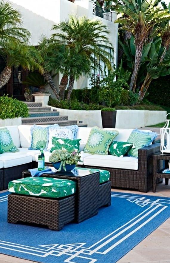 garten im sommer frisch gestalten und einrichten mit rattansofa braun, weißen polsterkissen, blauem teppich und weißen dekokissen mit grünem Blumenmuster