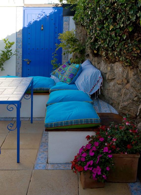 coole gartenideen für gartengestaltung im mediterranen Stil mit blauer gartentür, begrünter gartenmauer, ausgemauerter eckbank mit blauen kissen und diy couchtisch aus metall mit mosaik tischplatte