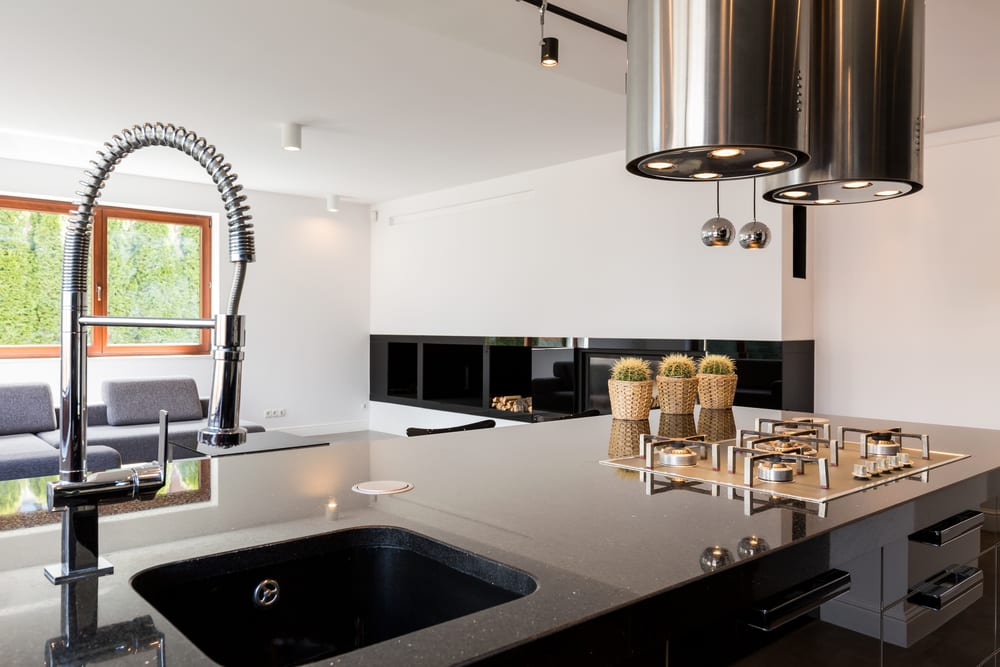 kleines wohnzimmer mit küche modern einrichten mit schwarzem kochinsel, runden deckenhauben über Gaskochplatte, ecksofa grau und schwarzer einbau-wohnwand