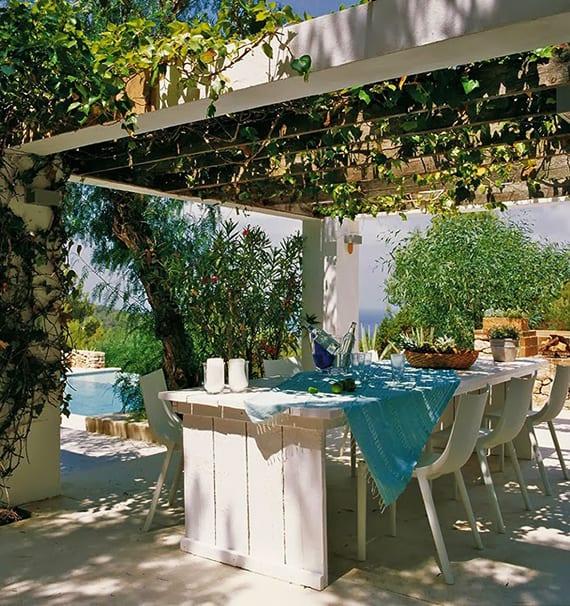 garten mit pool im meer stil gestalten mit begrüntem Holzpergola weiß, diy Esstisch aus Paletten mit modernen weißen Esstischstühlen und tischdecke hellblau
