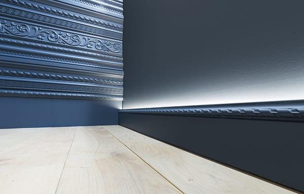 schicke raumgestaltung mit hellem holzfußboden, alu-fußleiste für wandbeleuchtung und kreative wandverkleidung mit dekorativen leisten in dunkelblau