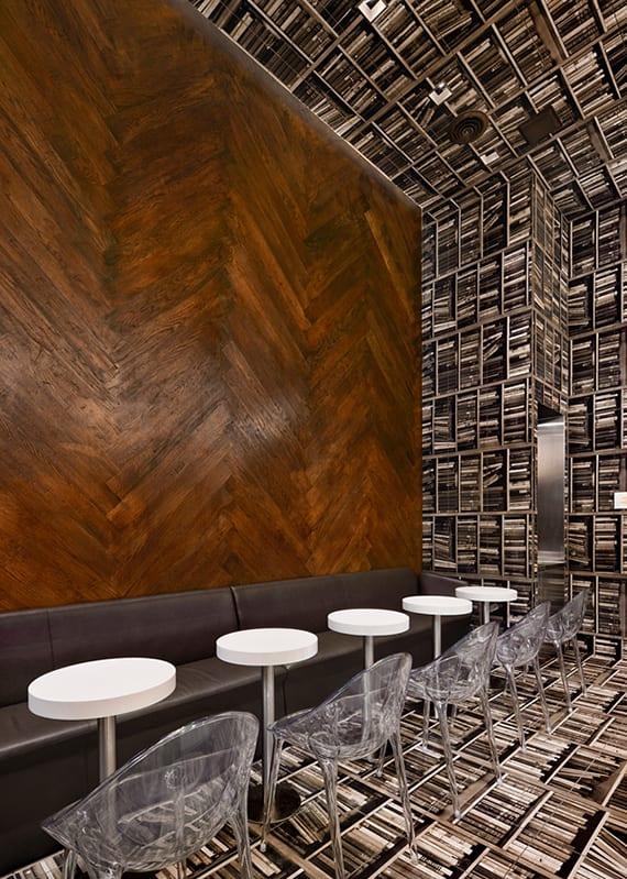 modernes interior design mit Akzentwand aus Holz, individuelle wandgestaltung mit Foto von Bücherregalen und ledersofas mit runden kaffeetischen weiß und stühlen aus acrylglas
