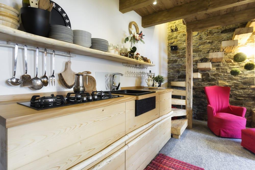 kreative Raumgestaltung kleiner Holzküche mit schwarzen Kochfeld und Spüle, Holzwandregal mit grauen Tellern, Akzentwand aus Naturstein, Holzbalkendecke mit LED Leuchten und kragstufentreppe aus holz