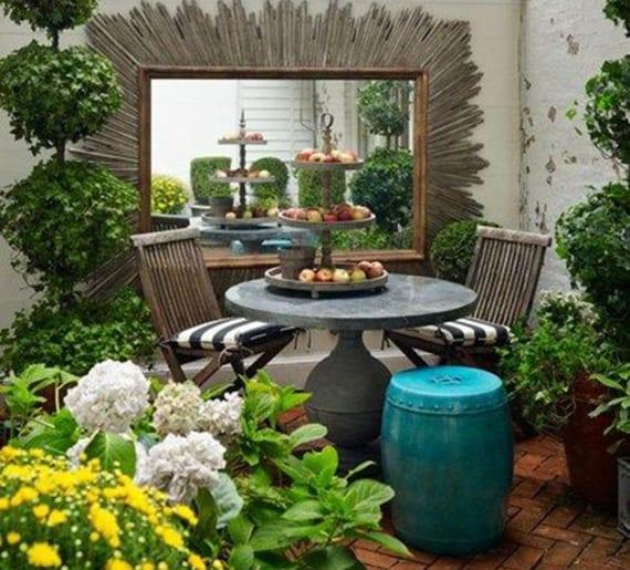 kleiner hofgarten kreativ gestalten mit spigel mit attraktivem Spigelrahmen, rundem Tisch aus Naturstein, holzklappstühlen mit gestreiften Sitzkissen, blauer hocker und fischgrätboden