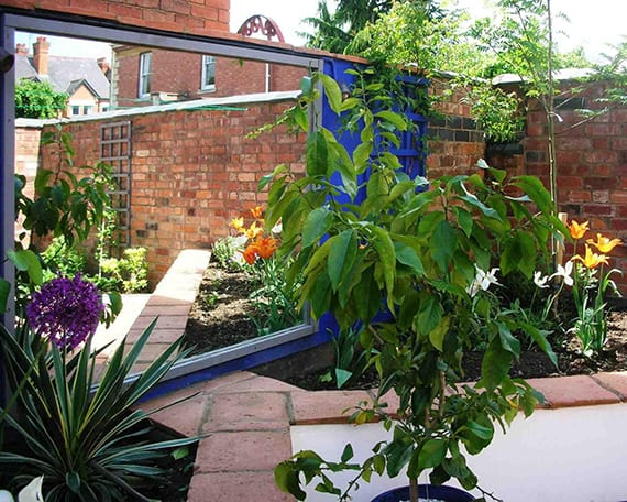 garten im hinterhof kreativ gestalten mit wandspiegel, wandfarbe blau, ziegelmauer und dreieckigen hochbeeten