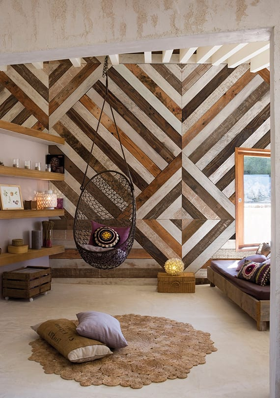 modernes interieur design wohnzimmer mit panoramatapete in holzoptik, holzwandregalen, diy sofa holz, schwarzem schaukelsessel und rundem teppich beige
