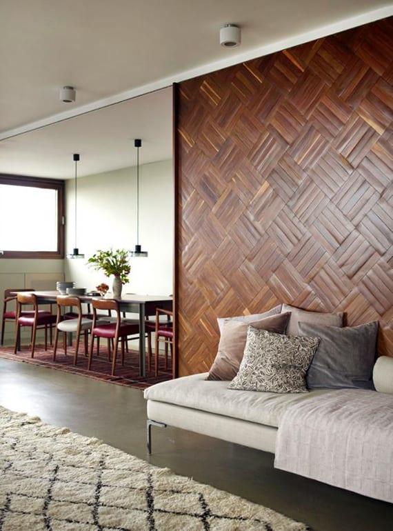 moderne wohnesszimmer mit betonboden, modernem sofa grau, holzesstisch mit klassischen holzstühlen mit lederpolsterung und kreative raumtrennung durch schiebewand verkleidet mit parkett