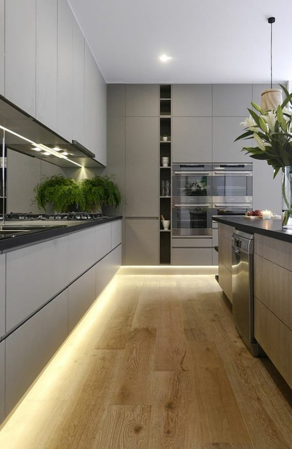 einrichtungsidee für moderne Küche in Grau mit holzfußboden, schwarzer Küchenarbeotsplatte und Spiegel-Spritzwand, Kochinsel, indirekter Bodenbelechtung
