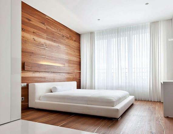 modernes schlafzimmer interieur mit holzfußboden, Holzwand hinter weißem Bett mit Lederkopfteil, moderne Wandbeleuchtung und weißen Gardinen