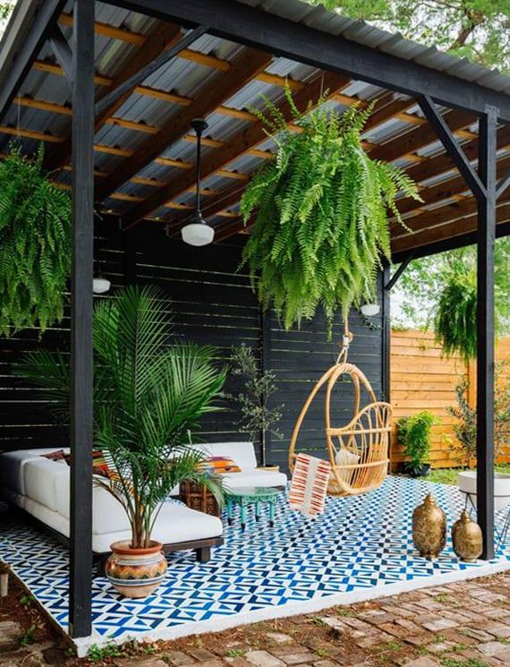 coole gartenideen für sitzecke im garten mit holzpergola schwarz, terrasse mit blauen musterfliesen, modernem ecksofa weiß, holzschaukelstuhl, hängenden blumentöpfen mit farn und marokkanischer deko