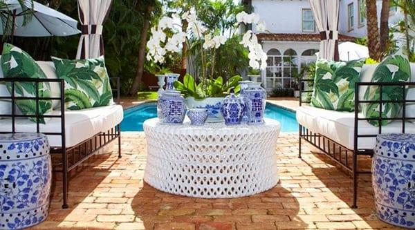 garten mit pool ellegant einrichten mit schwarzen gartenmöbeln aus metall , weißem polstern, rundem couchtisch weiß, japanischen gartenhockern und vasen aus porcellan und roten pflastern