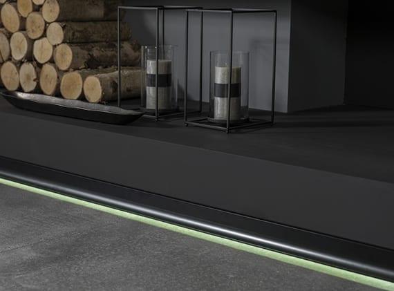 minimalistische Wohnzimmer schwarz mit Kamin, naturstenboden grau, wandfarbe schwarz, schwarz lackierter sockelleiste mit LED und kamindeko mit Rundhälzern, Metallkerzenhalter schwarz