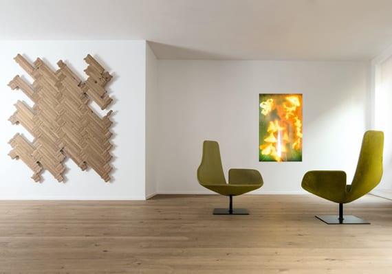 stilvolle raumgestaltung mit weißen wänden, holzfußbodenbelag, modernen Sesseln in grün und originelle wanddekoration mit parkett