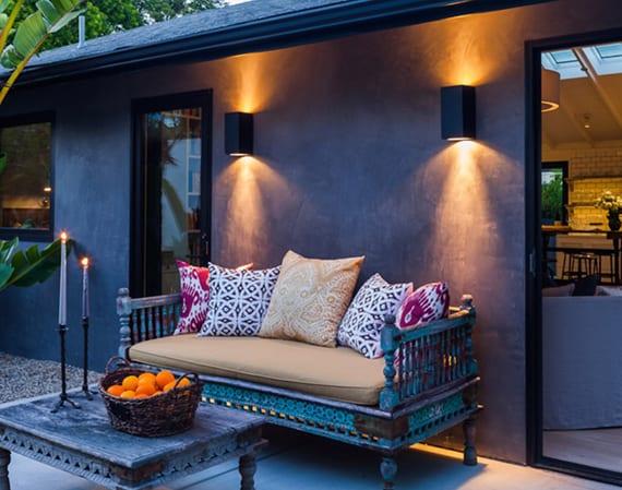 garten einrichten mit alten marrokanischen Holzmöbeln, bunt gemusterten kissen, metallkerzenhaltern und modernen wandlampen schwarz für gartenbeleuchtung