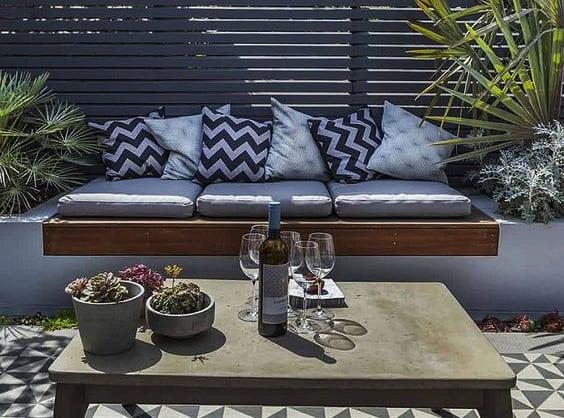 coole gartenideen für moderne gartengestaltung mit betoncouchtisch, ausgemauerter sitzbank mit hochbeeten, hochbholzsitz und grauen polstern,mosaikbodenbelag mit geometriefiguren in schwarz und gartenzaun grau