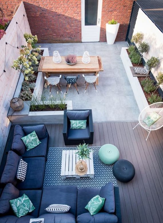 coole hofgarten idee mit holzterrasse, kuschelige Sitzecke mit Teppich, schwarzem Rattansofa mit dunkelblauen polstern, palett-couchtisch weiß, holzesstisch und hochbeete aus beton