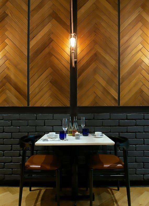 modernes interieur design im industriellen Stil mit holzwand im französchischen Fischgrätmuster mit schwarzen Fugen und dunkelgrauen ziegeln