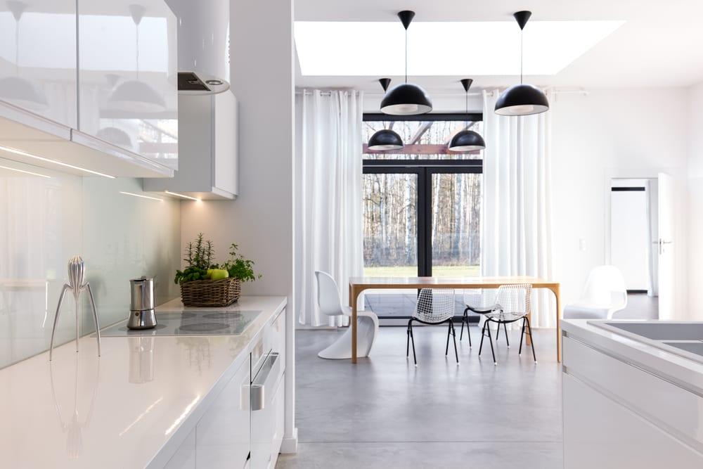 küche ideen für moderne küchengestaltung mit betonboden, weiße küchenschränken, kochinsel, holzesstisch mit designer esszimmerstüchlen unter oberlichter, schwarzen pendellampen und weißen gardinen vor verglasung mit antrazit fensterrahmen