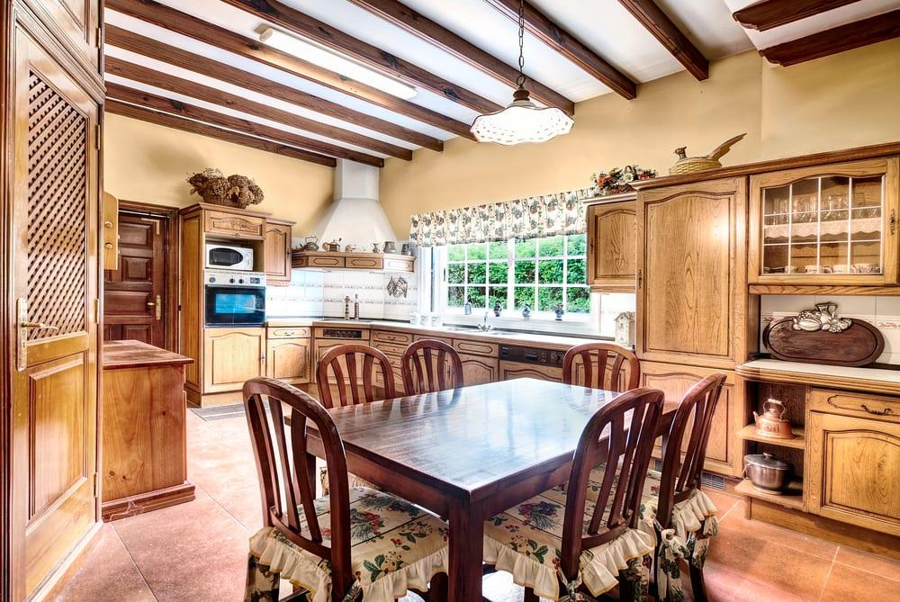 rustikale holzküche mit wandfarbe gelb, weißer decke mit holzbalken, weißen Sprossenfenstern, massivholztisch, rustikalen holzstühlen mit polstersitz