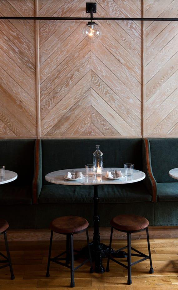 coole wandgestaltung ideen für cafes und restaurants mit holzwandverkleidung, kugel-wandlampen, grünem sofa und marmor kaffeetisch