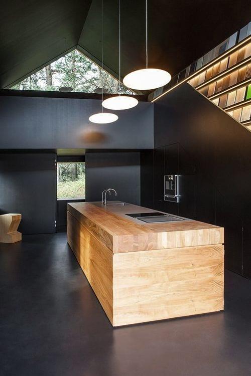 minimalistische kücheeinrichtung mit kochinsel aus massivholz und einbauküchenschränken schwarz_moderne raumgestaltung mit poliertem betonboden und wandverkleidung in schwarz, runde pendelleuchten, wandbücherregal mit indirekter beleuchtung und dreickfenster