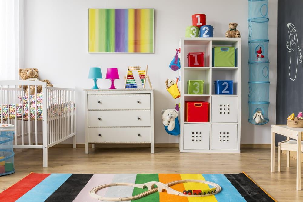 tolle babyzimmer ideen und moderne gestaltung mit weißem gitterbett, ikea regal mit bunten aufbewahrungskisten, holzkommode mit schubladen weiß, schwarzer Tafelwand, streifenteppich und kindertisch mit stühlen aus holz