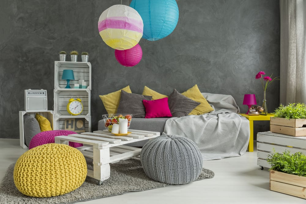 bunte und moderne kinderzimmer einrichten mit DIY regal aus weißen holzkisten, sitzecke mit diy palettentisch auf rollen, gestrickten sitzkissen in gelb, pink und grau, grauem teppich, beistelltisch gelb und farbigen pendelleuchten papier