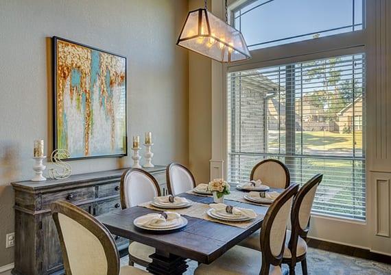 kleines esszimmer einrichten mit Buffetschrank und Esstisch aus massivholz, klassischen esszimmerstühlen mit weißer polsterung, vinatge pendellampe aus glas und metall und dunklem holzboden mit hellgrauem teppich