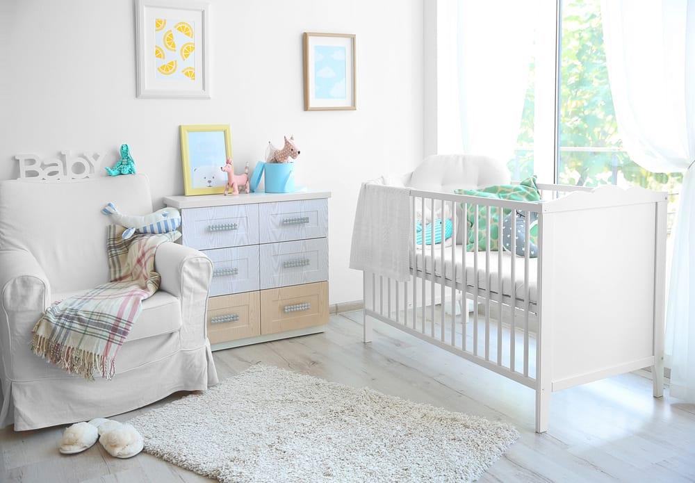 helles geschlechtsneutralles babyzimmer gestalten im weiß mit holzgitterbett, weißgrauem laminat in holzoptik, weißen gardinen und sessel mit bezug weiß und wanddeko mit bunten bilderrahmen