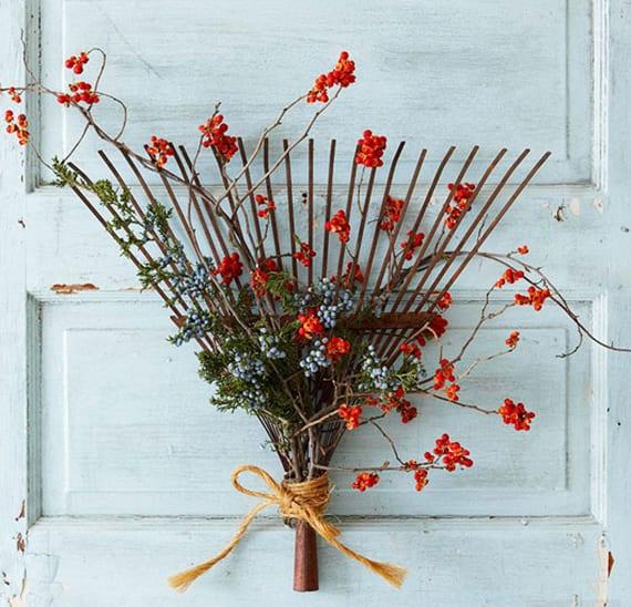 DIY Türdeko herbst mit altem Fächerrechen aus metall, immergrünzweigen und Beerenzweigen mit blauen und orangen herbstbeeren