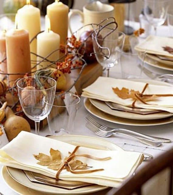 herbstliche tischdeko mit kerzen, birnen und zweigen auf holzplatte und cremefarbigen Servietten mit goldenen herbstblättern