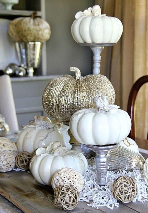 coole dekoideen herbst mit weißen Porcellankürbissen auf silbernen Kerzenhaltern, dekorativen kugeln aus holz und papierstreifen auf holzplatte