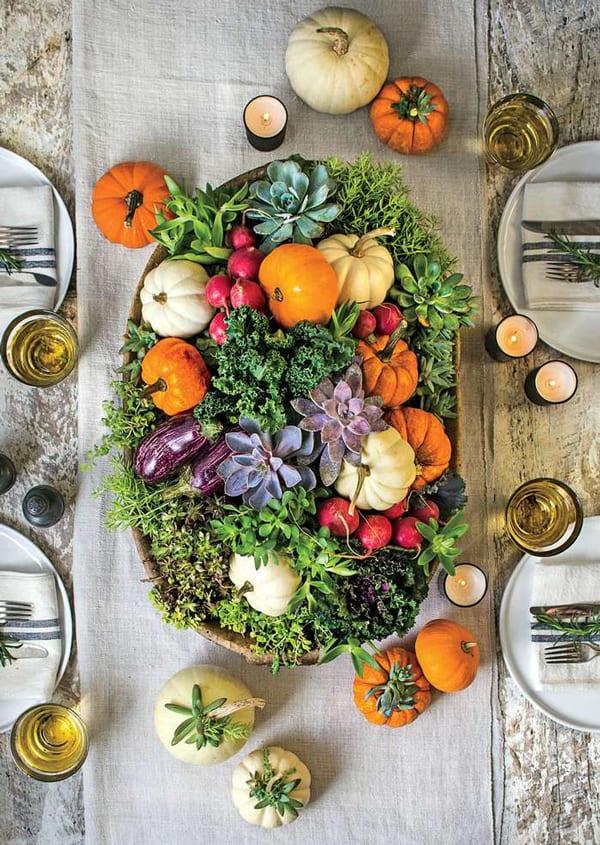 tisch eindecken und dekorieren mit Herbstgemüsen, kleinen weißen und orangen Kürbissen, Saftpflanzen und Kräutern in einer ovalen schale