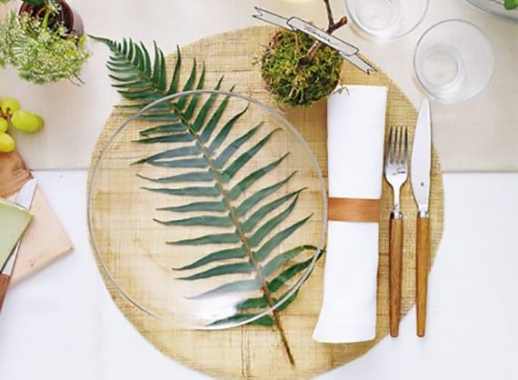 kreative tischplatz dekoration mit diy tischkarte aus moos, farnblatt, weißen stoffservietten mit holzserviettenring und rustikalem besteck