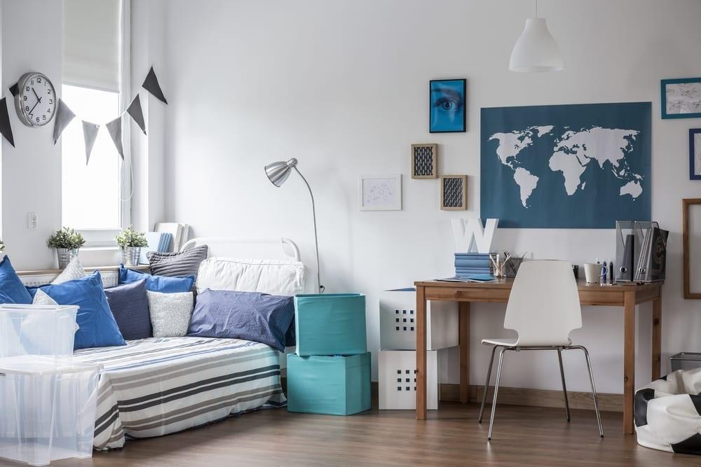 gestaltungsidee für modernes jugendzimmer Soffabett, holzschreibtisch mit weißem stuhl, fußball sitzsack, weißen und blauen aufbewahrungskisten und wanddeko mit blauen bilderrahmen und atlaskarte