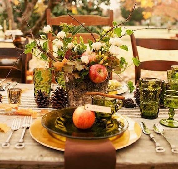 herbstliche tischdeko idee mit holz, äpfeln, rosen und zapfen für gartenpartys